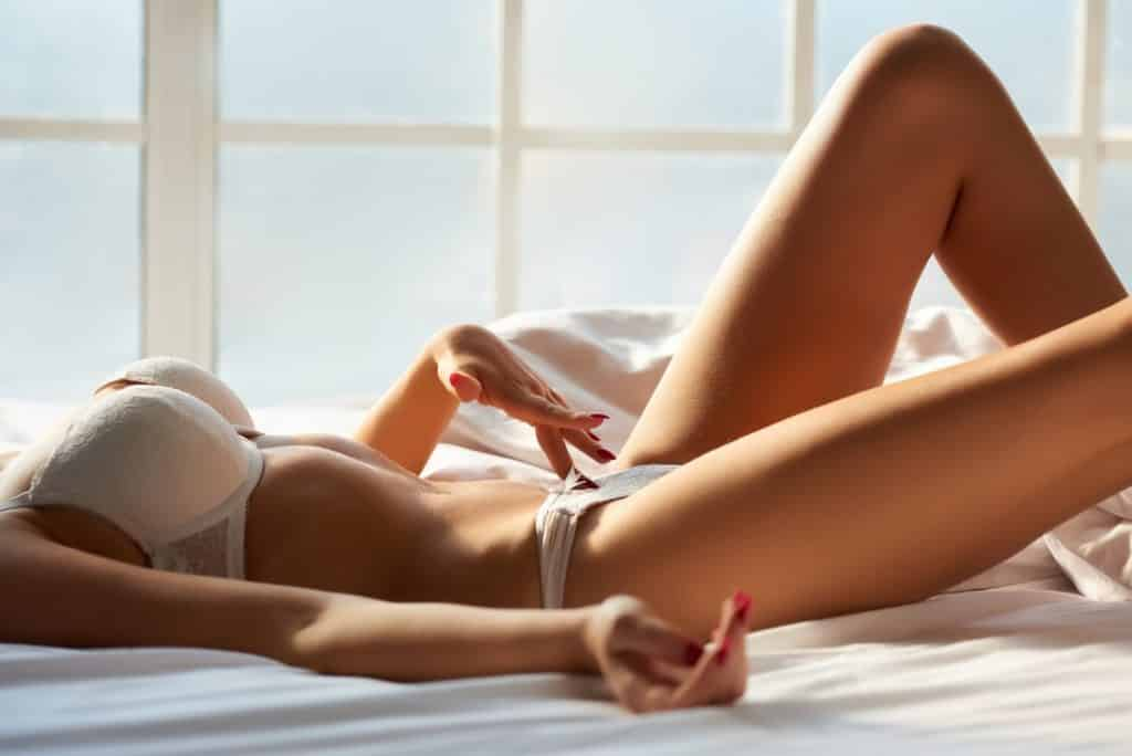 femme en sous vêtements allongée dans un lit, la main entre les jambes. concept masturbation du clitoris