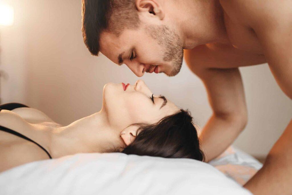 couple allongé au lit se regarde l'un l'autre
