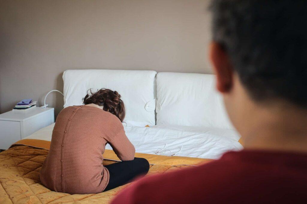 femme triste assise dans son lit. Son mari la regarde