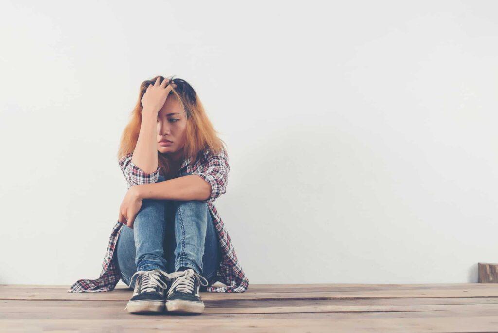 femme boulversée psychologiquement assise par terre