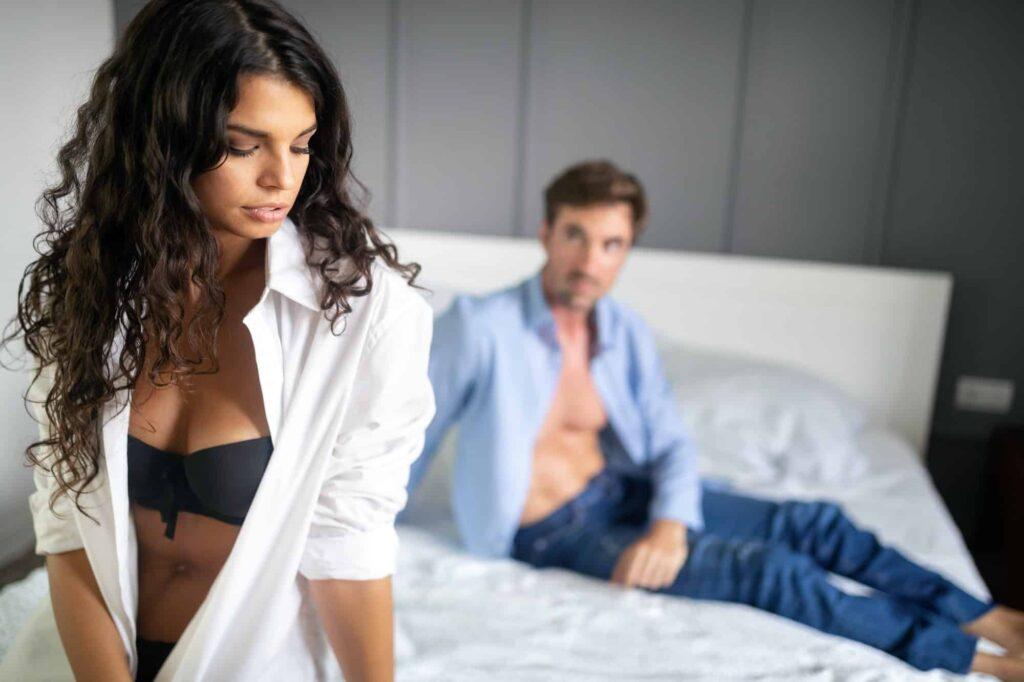 couple assis sur le lit ayant des problèmes sexuels