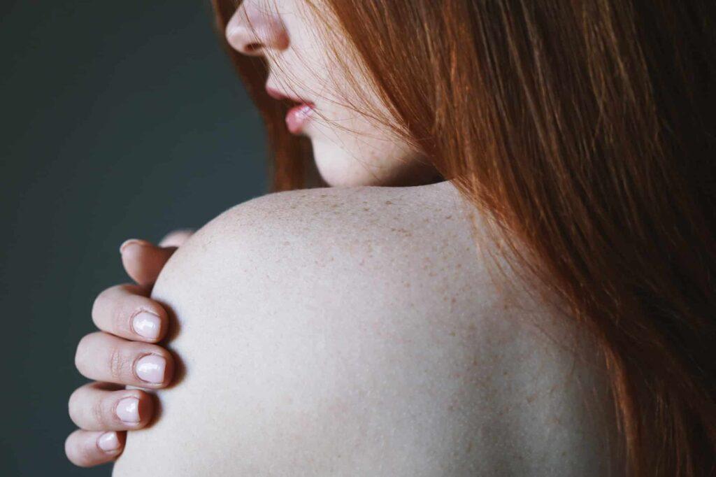 femme rousse nue se touche l'épaule